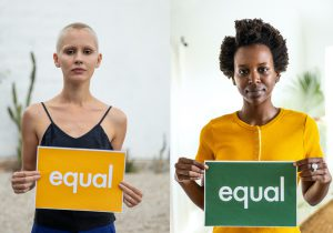 Group of women of different ethnicities standing holding equal signs