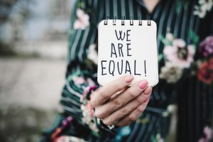 woman shows notepad with the text 'we are equal'